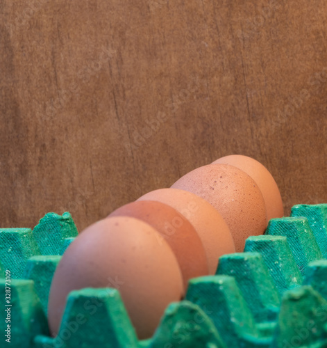 Photo Eggs in a row on a green cardboard made with recycled paper, close up
