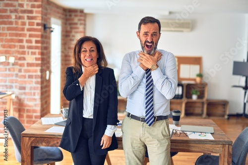 Two middle age business workers standing working together in a meeting at the office shouting and suffocate because painful strangle Wallpaper Mural