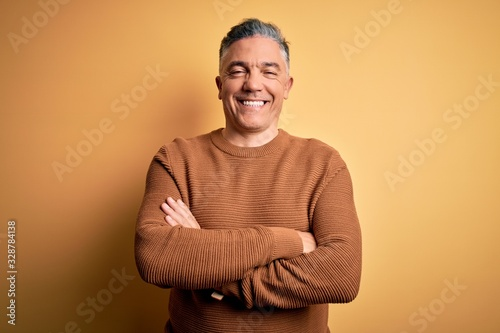 Fototapeta Middle age handsome grey-haired man wearing casual sweater over yellow background happy face smiling with crossed arms looking at the camera. Positive person. obraz