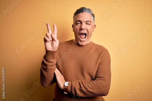Middle age handsome grey-haired man wearing casual sweater over yellow background smiling with happy face winking at the camera doing victory sign. Number two.