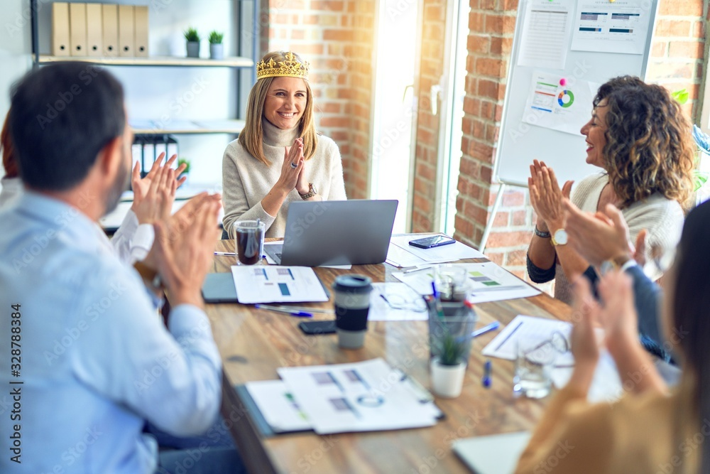 Fototapeta Group of business workers smiling happy and confident. Working together with smile on face applauding one of them wearing king crown at the office