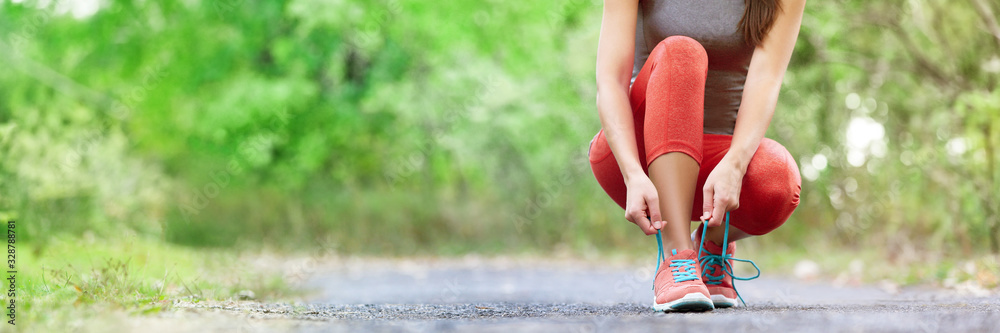 Fototapeta Exercise and sport running shoes runner woman tying laces getting ready for summer run in forest park panoramic banner header crop. Jogging girl exercise motivation heatlhy fit living.