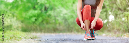 Foto Exercise and sport running shoes runner woman tying laces getting ready for summer run in forest park panoramic banner header crop