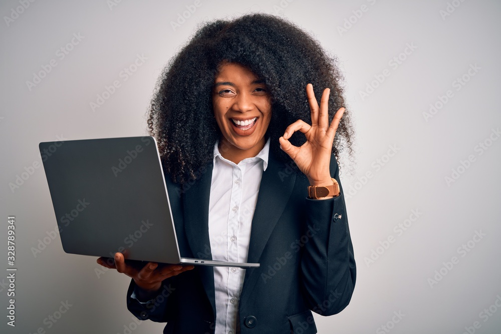 Fototapeta Young african american business woman with afro hair using computer laptop from job doing ok sign with fingers, excellent symbol
