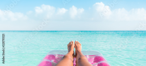 obraz PCV Beach summer vacation woman relaxing on pool float taking feet selfie pov of legs sunbathing relax on pink air mattress inflatable toy floating on blue ocean background panoramic banner.