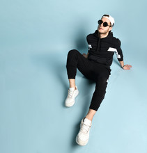 Man In Cap, Sunglasses, Black Tracksuit, Bracelet And White Sneakers. He Sitting On Floor, Posing On Blue Background. Close Up