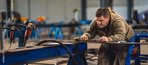 Obraz Industrial worker measuring the steel plate - fototapety do salonu