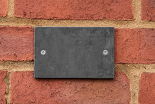 Blank Dark Clean Slate Plaque Affixed To A Seamless Brick Wall.