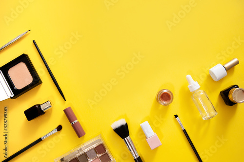 Make up flat lay on yellow background with copy space. COsmetics accessories araanged as a border for text