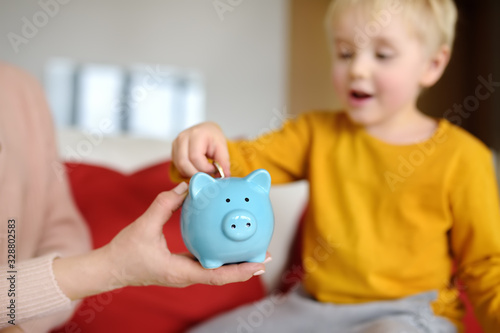 Fotomural Mother and child putting coin into piggy bank