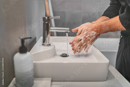 Washing hands with soap and hot water at home bathroom sink man cleansing hand hygiene for coronavirus outbreak prevention. Corona Virus pandemic protection by washing hands frequently. - 328804144