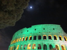 The Roman Colosseum Lit Up Green At Night For Saint Patricks' Day In Italy