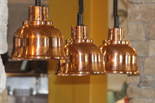 Three Shinny Light Shades In A Row Over A Meal Counter In A Pubs Restaurant. Retro Lighting Decor Over A Servery. The Lamps Are Copper Colour.
