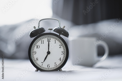 Fototapeta Closeup - Alarm clock have a good day with a cup of coffee on the bed background in the morning sunlight. obraz