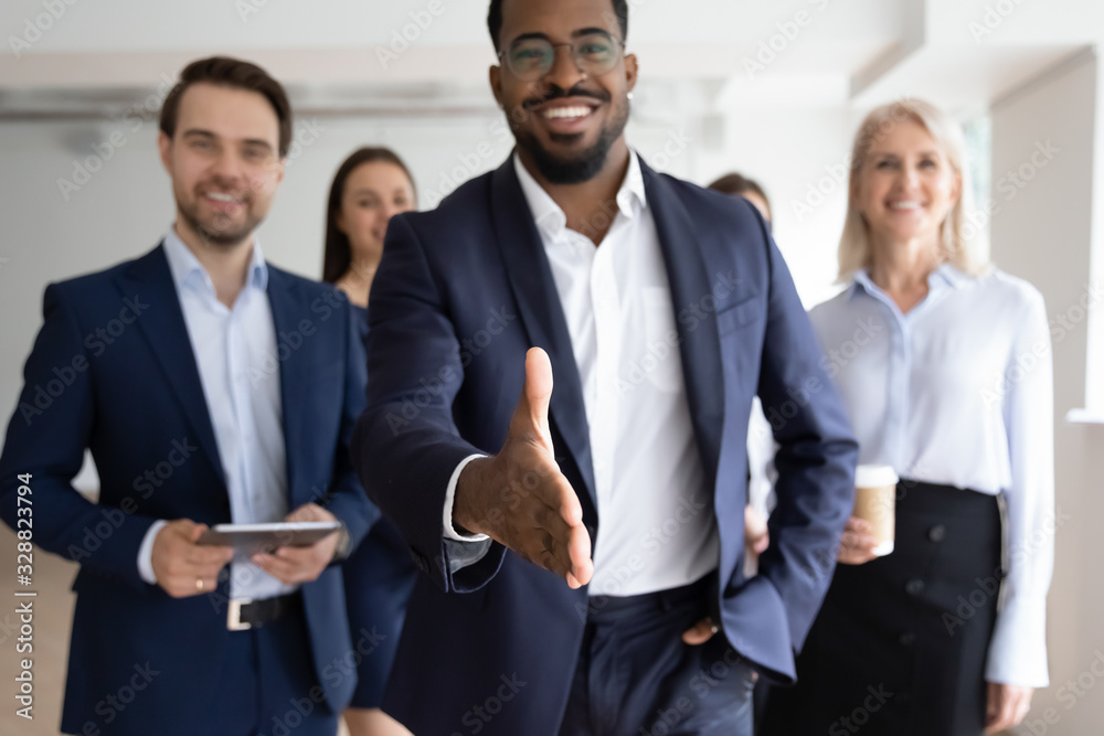 Fototapeta Group portrait of smiling multiracial businesspeople greeting newcomer to successful team, happy African American businessman stretch hand get acquainted with job applicant, recruitment concept