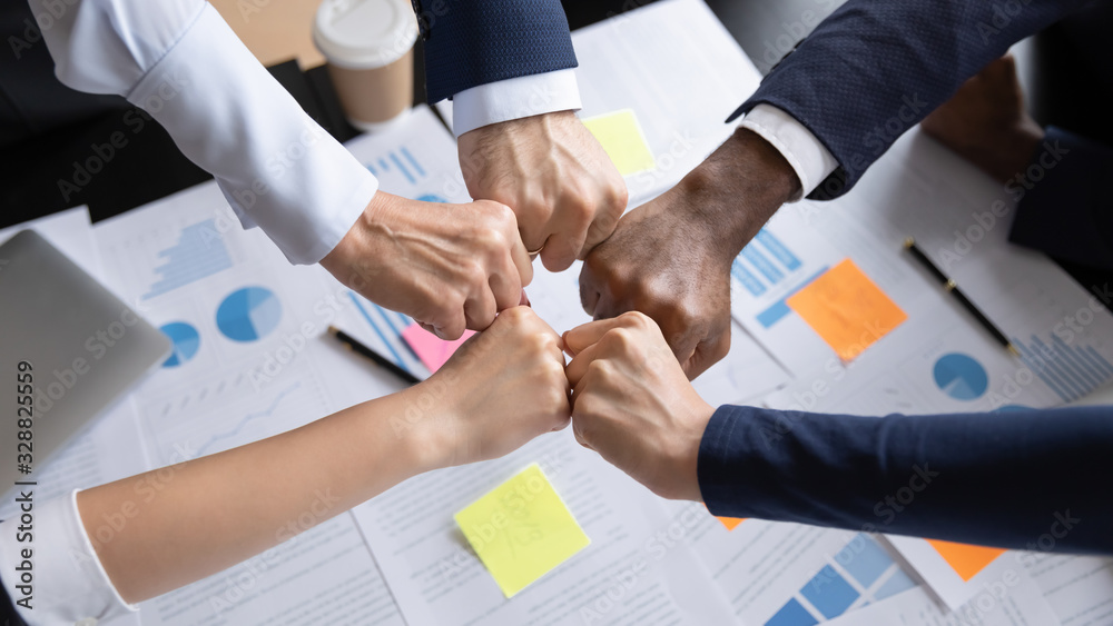 Fototapeta Close up top view of diverse multiethnic businesspeople give fists bump engaged in teambuilding activity at meeting, multiracial colleagues join hands show unity and support at briefing in office