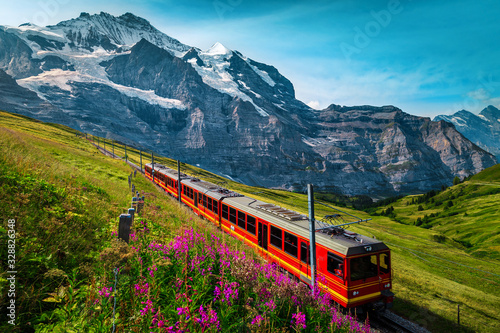 Obraz na plátně Electric passenger train and snowy Jungfrau mountains in background, Switzerland