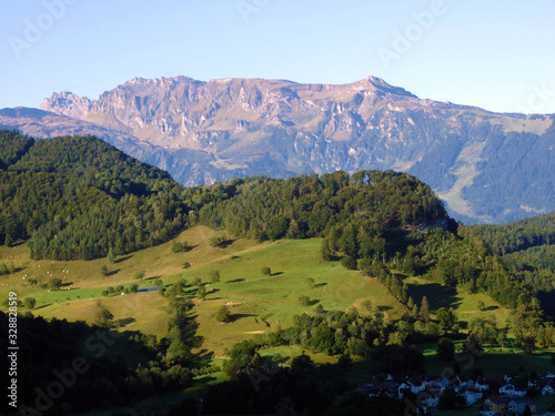 Fototapety, obrazy: Picturesque pastures, mixed forests and alpine peaks over the Rhine river valley - Balzers, Liechtenstein
