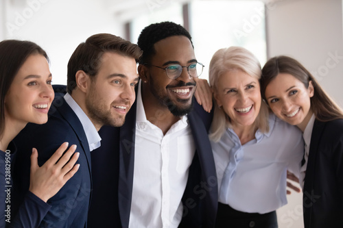 Smiling multiracial businesspeople embrace posing for group picture in office to Canvas Print