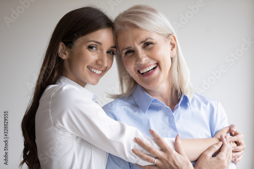 Fototapeta Head shot portrait of happy mature mother and grown-up daughter hugging cuddling posing for family picture together, smiling senior mom and adult girl show love and care, enjoy time together obraz