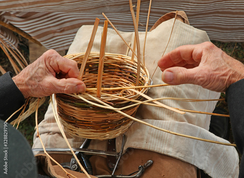 hands of an elderly man weave a wicker Wallpaper Mural
