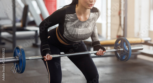 Valokuvatapetti Unrecognizable woman working out with barbell in sports club
