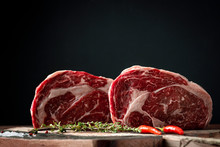 Raw Rib Eye Beef Steak With Pepper And Herbs On A Wooden Background In A Butcher Shop