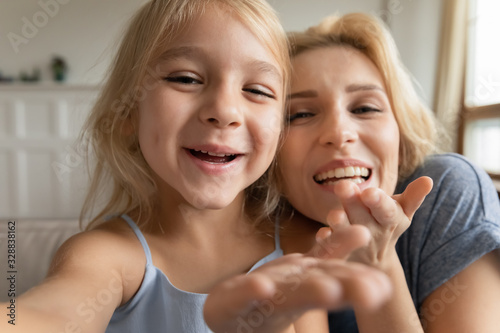 Photographie Cute little preschooler girl and young mother have fun make self-portrait pictur