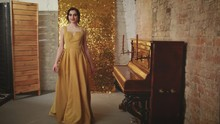Girl With Finger Wave Hairstyle In Gold Elegant Dress Goes Spinning Piano On Backdrop Shine Sparkle Glitter Screen. Holiday Stylized New Year In Style Retro Great Gatsby Women Vogue Fashion Old 1920