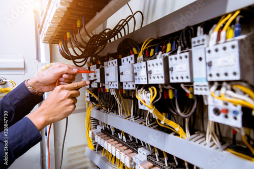 Fotomural Electrician measurements with multimeter testing current electric in control panel