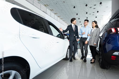 mata magnetyczna Car Sales Manager Showing Auto To Buyers In Dealership Store