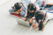 canvas print picture - Three aisan children, Three sister, lay on the floor and use a laptop to do their schoolwork.