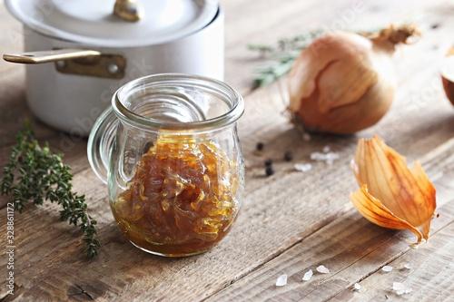 Fotografiet Homemade onion marmelade (jam) in glass jar on  rustic wooden table
