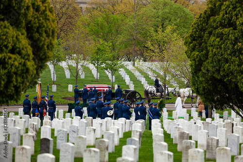 Photo US military cemetery on foreground and burial procession on background at spring