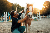 Fototapeta Zwierzęta - Young attractive male veterinarian enjoying with adorable little pony horse.