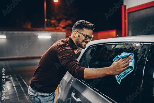 mata magnetyczna Young man washing his car in the evening at car wash station using high pressure water.