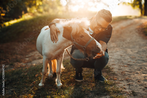 Fotomural Young attractive male veterinarian examining and feeding adorable little pony horse