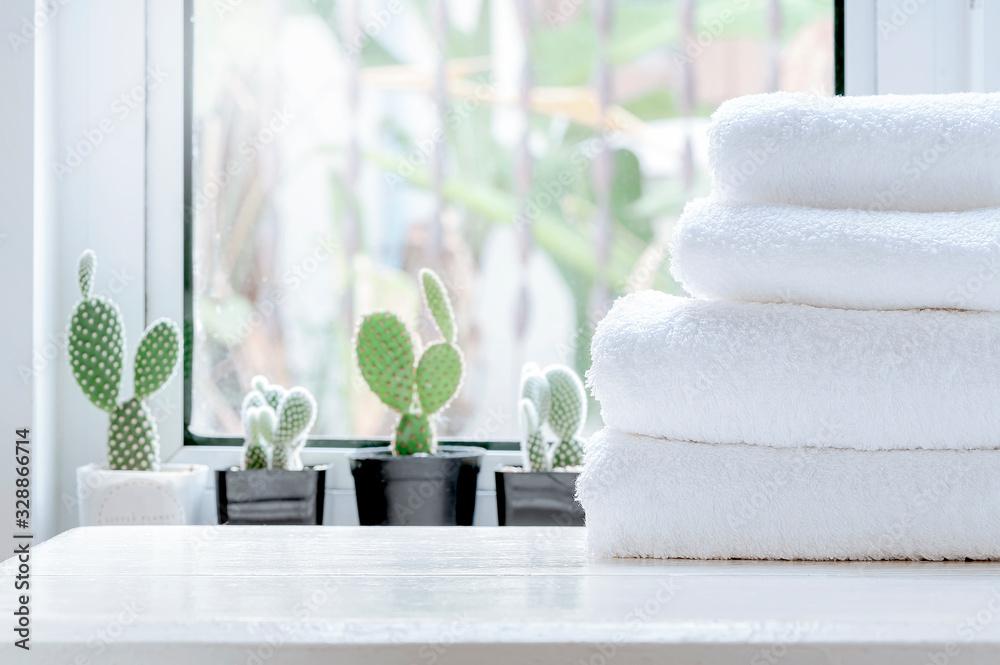 Fototapeta Clean towel on white table near window sill.