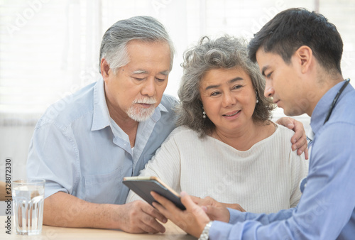 Fotografiet Elder senior old asian couple meeting  specialist professional caucasian doctor visit at home consultant two retirement patient after checkup,health care and medical concept