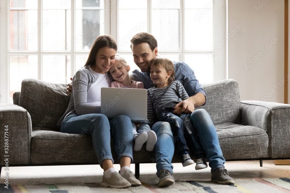 Fototapeta Happy young couple resting with children siblings on sofa, watching cartoons comedian movie on laptop. Overjoyed spouses having fun with joyful cute kids son daughter, using computer at home.