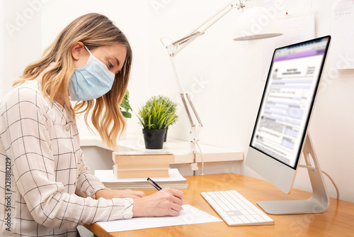 Obraz Young business woman working from home, wearing protective mask - fototapety do salonu