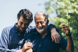 Fototapeta Na ścianę - Adult hipster son and old senior father stay for work at home, two generations have a beard talking together and relaxing with smile, happy enjoy living to isolation quarantine at home, father's day