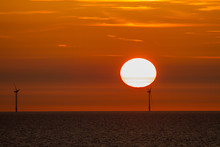 Two Wind Turbines In The North Sea In Front Of The Sun At Sundown With A Red Sky