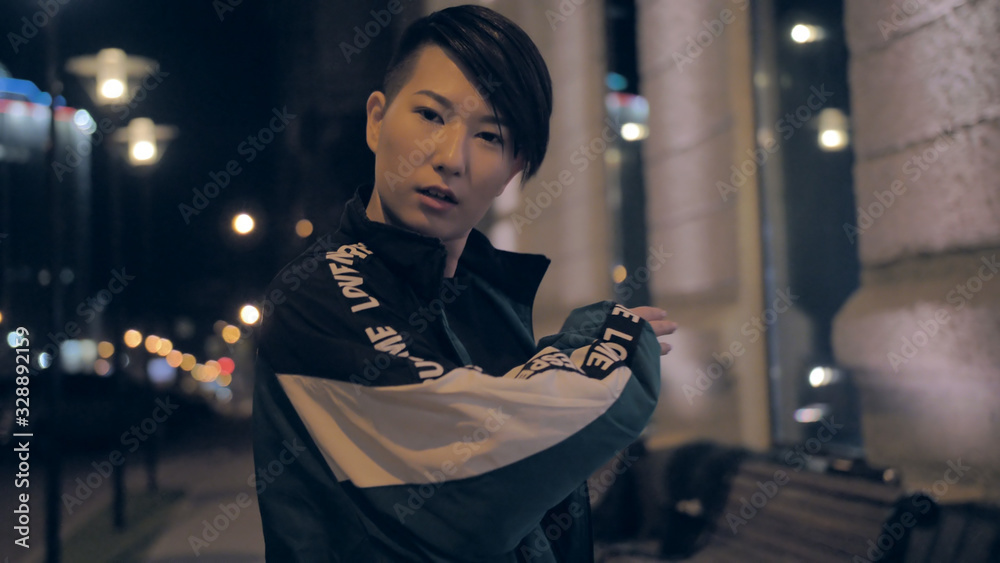 Fototapeta Very stylish asian girl dancing on a city street at night. Impressive Korean girl