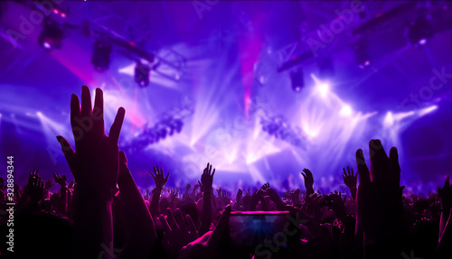 Happy people dance in nightclub DJ party concert and listen to electronic dancing music from DJ on the stage. Silhouette cheerful crowd celebrate New Year party 2020. People lifestyle DJ nightlife. - 328894344