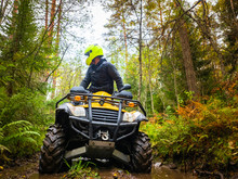 Human On The ATV. A Man Rides Through The Forest On A Quad Bike. Riding An ATV Through Mud. Off-road Driving. Extreme Sports. The ATV Driver Is Looking Back. Concept - A Contest On Quad Bikes
