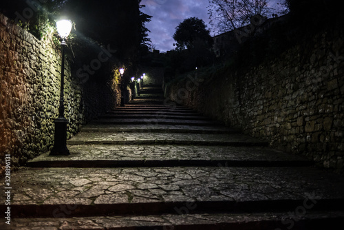 Dark medieval cobbled alley at night with several street lamps providing light Canvas Print