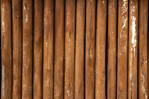 Background of thin brown shabby old wooden logs. Copy space.