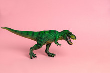 Green Dinosaur Toy With Open Mouth On A Pastel Pink  Background