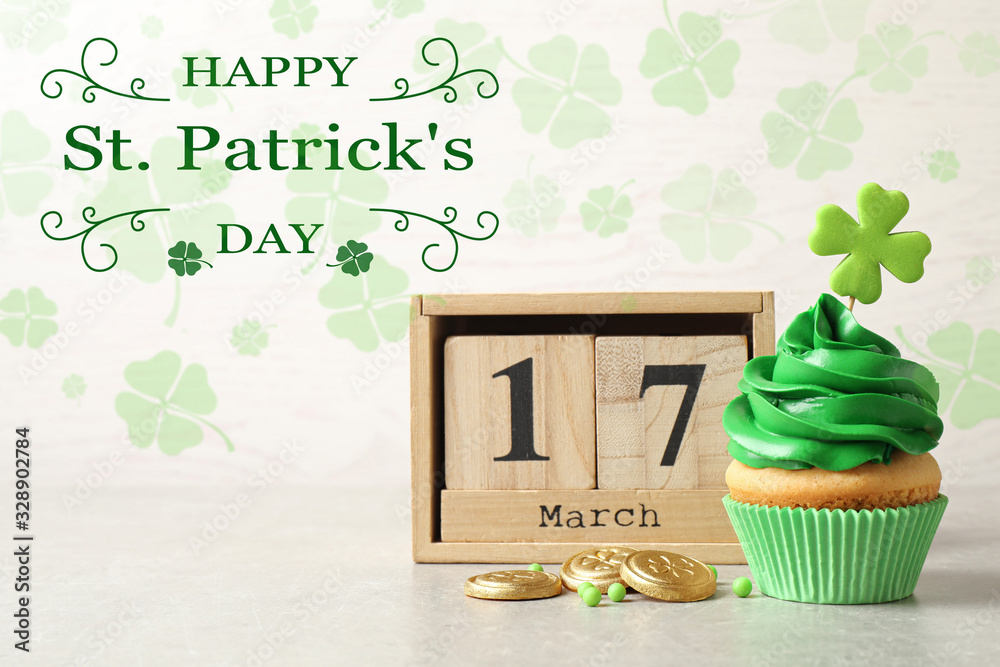 Fototapeta Delicious decorated cupcake, wooden block calendar and coins on light table. St. Patrick's Day celebration